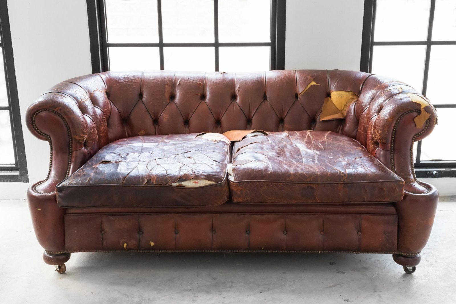 Old leather couch in need of furniture removal services
