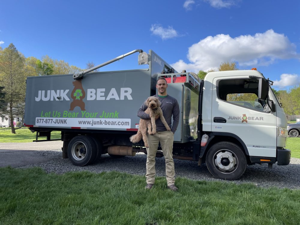 Junk Bear team member in front of truck with dog